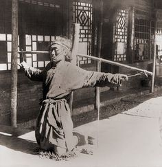 Chinese prisoner kneeling on chains, with his ankles in stocks, while his arms are tied by the thumbs to a pole supporting his arms. Moukden, China. Circa. 1900.