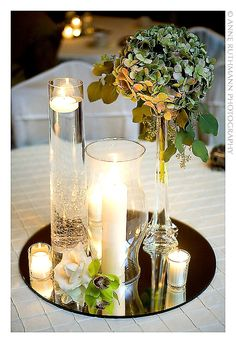 tall clear glass with tea lights floating ,  other candle in a hurricane shade , smaller ones in different votive holders