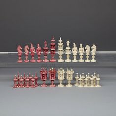 """FRENCH TURNED AND CARVED IVORY CHESS SET, DIEPPE, 19TH CENTURY one side stained red with white, the royal pieces with flaring pierced gallery rails, bishops as three quarter length uniformed officers, knights as horse heads and rooks as elaborate turreted castles, king height 3.9"""" - 9.9 cm"""