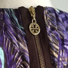 Tori Burch Silk Shell; Peacock Print; Size 2 This is a beautiful silk shell by Tory Burch. It has a beautiful peacock feather print with several shades of purple, lavender, blue, & gold. Features exposed gold back zipper with signature Tory Burch logo zipper pull. Only worn once or twice--EUC. Extremely versatile shape--can be worn tucked into a pencil skirt, with a suit to work, or even untucked with dark cuffed skinnies and platform mules. Possibilities are endless, and the quality of TB…