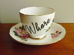 Rosy Ho    Reworked vintage English Delphine bone china teacup and matching saucer set adorned with pink roses and featuring a scalloped rim and