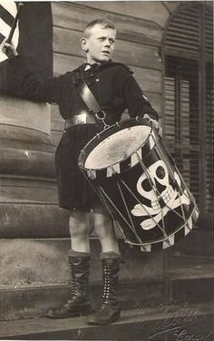 "A studio portrait of German Jungvolk boy in Cassel playing a drum marked with a skull and crossbones, reminiscent of the imagery of Gunther Grass' ""The Tin Drum"""