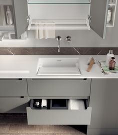 Combining the Laundry Space collection with Scavolini's Idro bathroom range makes for a practical and ergonomic setting. Notice the practical handle grips shaped into the door and the Polished White Mineralmarmo® top: outstanding solutions and prestigious design.