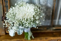 The bridesmaids carried simple bouquets with large white spider mums surrounded by bunches of baby's breath. From An Elegant Multicultural Wedding at Oceanstone Seaside Resort in Indian Harbour, Nova Scotia