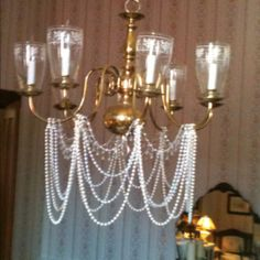 I used pearl, clear and faux crystal garland from the dollar tree to dress up the chandelier in my dining room.    Very inexpensive way to add a little shabby chic!