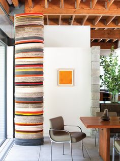 In the dining room,  the striped column is by artist Phyllida Barlow. The orange painting is by Walter Darby Bannard. The aluminum chairs were a vintage discovery by Fernandez and Clements at Lucca Antiques and the custom dining table is Douglas fir.