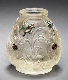 A Mughal gem-set rock crystal Jar  Northern India, late 18th Century with pear-shaped body, short foot and short cylindrical neck with two concentric grooves, the body carved in relief with a frieze of trailing floral stems, the flowerheads set with gem stones within gold mounts, with gem-set birds hovering between the stems  7 cm. high