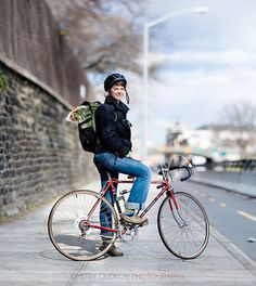 Young woman in jeans, dark jacket, with road bike and backpack.