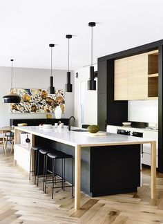 Stunning, modern kitchen with black and wooden cabinets, hung artwork and unique herringbone floors | Austin Design Associates