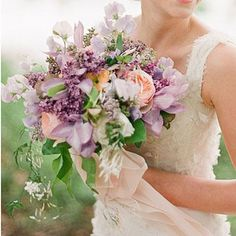 Lilac Bouquet | Sweet peas, lilacs, garden roses, ranunculus, and clematis combined for this soft and sweet bouquet. | SouthernLiving.com