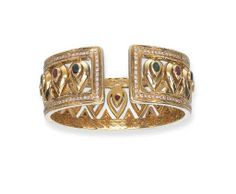 A GEM-SET CUFF BRACELET  The openwork band designed as a series of polished drop-shaped motifs, each set with an oval-cut sapphire, ruby or emerald, to the circular-cut diamond borders, 6.0 cm. diameter