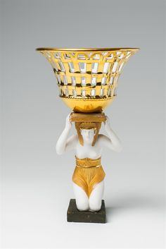 A Parisian porcelain figure of an Egyptian carrying a basket Fired in three parts and screw-mounted. Gold mark Dagoty à Paris. The bracket restored. A diagonal crack to the basket. H cm. Les Dagoty Manufactory, ca. The Saleroom, Empire Style, Art Auction, Parisian, Vintage Antiques, Art Decor, Restoration, Basket, Clay