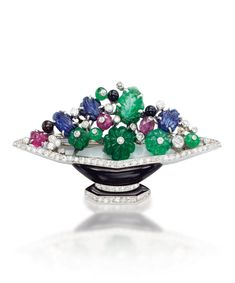 VAN CLEEF & ARPELS - AN EXQUISITE ART DECO MULTI-GEM 'VASE DE FLEURS' BROOCH, CIRCA 1930. Designed as a stylised black enamel and diamond vase with carved sapphire, onyx bead, carved ruby and fluted emerald flowers, signed Van Cleef & Arpels, numbered.