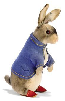 A STEIFF LARGE PETER RABBIT (4428,6), white and grey velvet, black boot button eyes, red felt behind, pink stitching, blue felt coat with two pockets, yellow stitched piping and ridged brass buttons, red felt slippers with yellow stitched piping and leather soles printed with Steiff trademark and FF button, circa 1908 --10in. (25.5cm.) high