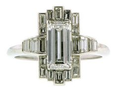 Art Deco Emerald Cut 1.25 HIVS1 Baguette Frame Platinum Engagement Ring centering and emerald cut diamonds weighing app. 1.25ct within a geometric baguette set frame. Fashioned in platinum. $9500
