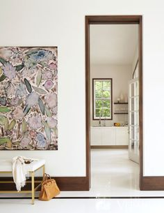 """In a bold stroke, Jan Showers suggested painting the entry hall black. """"It sets off the glossy white of the rooms on either side,"""" she says, and is a powerful visual cue to the staircase down the hall."""