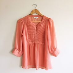 """Banana Republic Sheer Peach Blouse Beautiful and elegant peach colored sheer blouse from BR. Tuxedo style placket with button loops. Loose, billowy 3/4 sleeves with two button bands. Size S with a very loose fit - I'm a 6/8 and this fits well. Bust is 19"""" and length is 26"""". EUC - no holes, defects, or stains. Material tag has been removed but this feels like a polyester. Very sheer - recommend a cami underneath or a jacket over this pretty blouse. Thanks for looking! Banana Republic Tops…"""