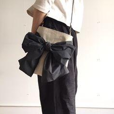 持ち手部分に取り外しができるリボンモチーフが付いたトートバッグを作りました。大きめのリボンは、手で持っても、腕にかけても、フェミニンにまとまるフォルムに、バッグ部分は、少し横長&浅めの手提げサイズで、すっきりシックな雰囲気です。色・素材は、持ち手・リボンには、濃いめネイビーストライプのコットン生地を、バッグの本体は、ハリのあるネイビーの帆布、内側にはベージュのコットン生地を使用しています。リボンモチーフは、結び目の部分がテープのようになっていて、クルっと持ち手を巻いてマジックテープで留め外しをすることができます。バッグの内側は内ポケットが一つ、スナップボタンが一つ付いています。===☆ 発送について ☆===☆こちらのリボントートは現在、2〜7営業日以内の発送を予定しています(*土日祝日を除く)。*簡易梱包の場合、定形外郵便(規格外…