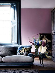light plum living room walls and blue sofa. #bluesofa #bluecouch #floralpillows #throwpillows #pinstriped #purplewalls #lavender #plum #purplepaint #wallpaint #wallcolor #pastels #jeweltones #purpleandblue #flowers #floralarrangement