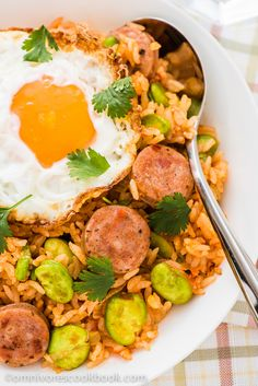 TOMATO FRIED RICE WITH SAUSAGE  (Serves: 2) ==Ingredients== 1 medium-sized tomato, 1 T vegetable oil, 1/2 c chopped sausage, 1/2 c fresh broad beans (or peas), 3 T scallion (or green onion), 2 T ketchup (or tomato paste), 1 t sugar or to taste, 2 c cooked rice, 3/4 t salt or to taste, (optional) 2 eggs ====