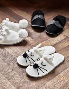 Three pairs of customized slippers sit on the floor.