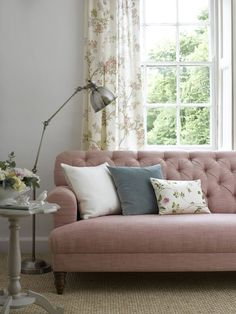 Country cottage living room scheme: Choose a super comfy sofa that has a classic style with curvy arms and button back detailing. Team with pretty floral curtains and matching cushions in similar tones to keep the look cohesive. Lighting is key especially for avid readers - opt for a design that has a timeless appeal and one that can be adjusted for ease of use. (Photo by Pooky). Get more styling tips at housebeautiful.co.uk