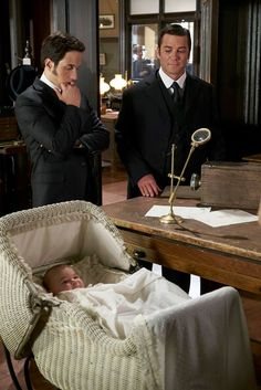 Roland rests in his pram while Crabtree (Jonny Harris) and Murdoch (Yannick Bisson) discuss the case