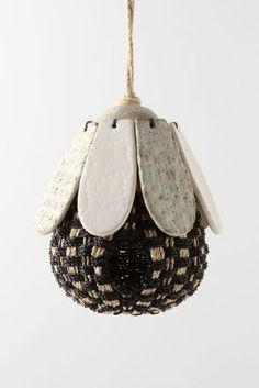"""Buzzy Birdhouse. Textured stoneware petals shelter a macrame hive to let one set of winged-things act like another. Earthenware, steel, palm leaf. 7.75""""H, 6.25"""" diameter; 9"""" rope. via Anthropologie"""