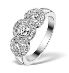This stunning trilogy diamond halo engagement ring is a glamorous contemporary take on the grand vintage jewellery of the Roaring Twenties. It showcases a beautifully sparkling round solitaire and two accent diamonds, each framed by an exquisite pave halo. Set in fine 18K white gold, it's the perfect ring for an elegant bride who loves luxury. £1359.00