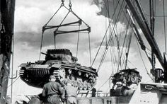 """Unloading German military equipment from the Afrika Korps at the port of Tripoli, North Africa. In the foreground PzKpfw III Ausf G medium tank. Afrika Korps commander Erwin """"Desert Fox"""" Rommel. Location: Tripoli, Libya, North Africa Time taken: 1941"""