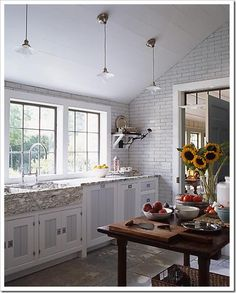 If you look closely at this kitchen (above) the stone countertop and flooring and subway tile have a green undertone while the interior panels of the doors have been painted a blue-gray.