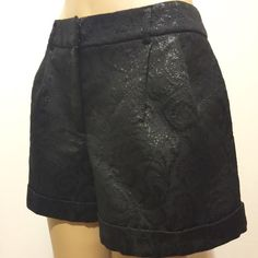"""Pins and Needles Dressy Black Shorts HP 8/11 FOR TOTAL TRENDSETTER  HP12/2 FOR DOWNTOWN CHIC  Black shimmery embossed fabric . 1 1/2""""contour waistband with belt loops, fly closure, double pleats at front, darted back, cuffed him. Fully lined.  60% poly 16% cotton 12% rayon 12% lurex Lining 100% poly  Dry clean only Urban Outfitters Shorts"""