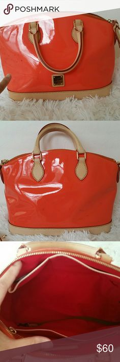"""Dooney & Bourke Patent Leather Domed Satchel Preown. Has black marking on the front and back of purse. Very noticiable.price reflects flaws Color clementine. .Patent leather body, double handles, adjustable and detachable shoulder strap, zipper closure, metal plated logo, four bottom feet, goldtone hardware Signature red lining, back-wall zip and slip pockets, two front-wall slip pockets, key keeper Measures approximately 10-3/4""""W x 9""""H x 6""""D with 4"""" handles and a 21-1/2"""" to 23-1/2"""" strap…"""