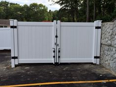 White solid privacy vinyl dumpster enclosure and 12' wide double gate with gate wheels install by SNK Fence
