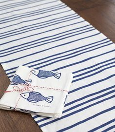 Blue marine print on white linen, table runner with co-ordinating fish napkins.