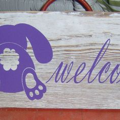 """Rabbit / Bunnies are so cute.  A great sign to ad to your favorite spring summer wreath or just put it on the door by itself ads a warm inviting feel to your home or business.  Approx. Measurement: 12"""" x 5.5""""  Materials: Wood, White Paint Distressed Sign , Purple Vinyl Lettering/Rabbit, Jute Cord  Like the sign but wish to have a different color or different words. We do accept custom requests. Please contact us. ********************************************************** P..."""