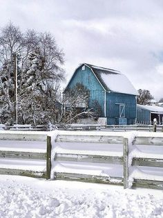 Blue barn stands beautifully in the crisp white snow.
