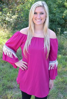FUCHSIA TUNIC WITH FRINGE DETAIL  34.00 Off the shoulder tunics are always a hit. This one features an aztec pattern with fringe detailing on the sleeve. Pair this top with your favorite skinny jeans or comfy leggings and booties to complete your look.