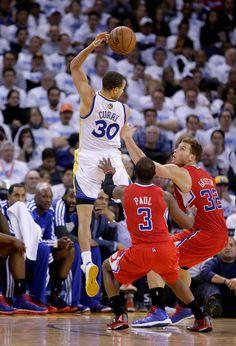 buy online 33260 660a4 Stephen Curry of the Golden State Warriors passes the ball behind his head  over Chris Paul and Blake Griffin of the Los Angeles Clippers at Oracle  Arena on ...