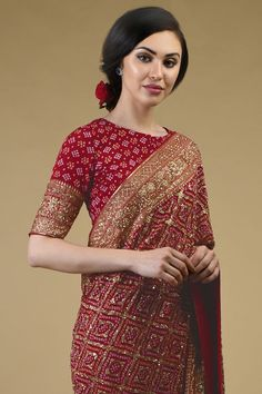 From our heritage bridal collection, this red Masterpiece saree is a coming together of exotic Banarasi Zari hand weaving, handcrafted exquisite Gujarati Bandhej and intricate rich heritage Zardozi hand embroidery. Take a close look at the stunni Indian Gowns Dresses, Indian Fashion Dresses, Dress Indian Style, Indian Designer Outfits, Designer Dresses, Saree Blouse Neck Designs, Saree Blouse Patterns, Fancy Blouse Designs, Stylish Blouse Design