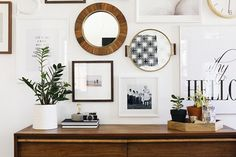 Minimalist styled vignette with a vintage wood dresser, a plant and a mis-match gallery wall