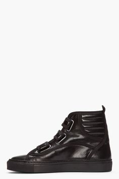 RAF SIMONS //  Black leather velcro high-tops  32287M050007  High-top leather sneakers in black. Round toe. Velcro closures at vamp. Logo stamp at upper Velcro strap. Padded collar with pull loop. Black rubber sole with textured sole walls at toe and heel. Tonal stitching. Upper and lining: leather. Sole: rubber. Made in Portugal.  $610 CAD