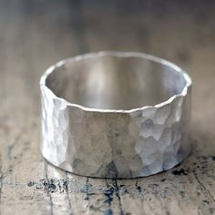 """Hammered wide band sterling silver ring. Unique hammered pattern silver ring that is a perfect men's wedding ring or an awesome everyday ring for men or women. The ring measures about 3/8"""" wide or 9mm. This ring is also available in a narrow width here and as a wedding set here. The rings are available in 14 karat yellow gold, 14 karat white gold, 14 karat rose gold and 14k palladium white gold. The 14k white gold has a bit of nickel it in. If you would like a nickel free opti..."""