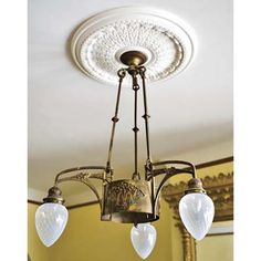 """To give the new plastic ceiling medallion an aged look that blends with the 1920 ceiling fixture it surrounds, we plastered and then painted it.""  - a DIY tip from a couple whose renovated 1897 Brick Queen Anne townhome in Baltimore Maryland was featured in This Old House. vintage antique light fixtures, DIY painting tips, being creative on a BUDGET."