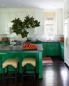 Gorgeous emerald green painted classic raised panel cabinets, accented with dark hardwood floors, white upper cabinets and glossy black countertops.