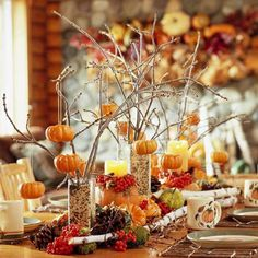 Tiny little pumpkins hanging on branches. Nice Thanksgiving table centerpiece.