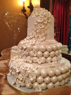 Three tier wedding cake covered in fondant. White chocolate cake balls cover the middle and bottom tiers. Cascading hydrangea blooms made fr...