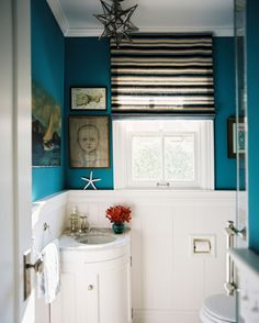 vintage style bathroom with pop colors choice blue walls decorated by wall arts white baseboard unique hang lamp small glass window with white frame of Great Choices of Fancy Colors for A Small Bathroom
