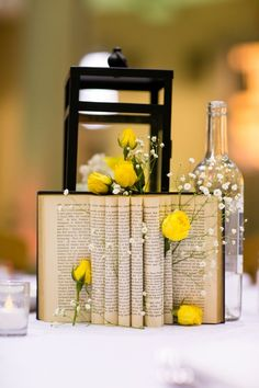 Book, Bottles and flowers - great centerpiece idea! Yellow and Grey Wedding by Nicole Chan Photography - KnotsVilla