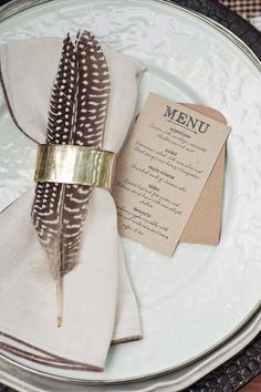 Place settings. Simple elegance. Love the delicate details of the feather with the bold pewter napkin ring
